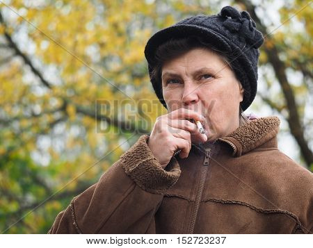 Woman at the age of smoking a cigarette. Social problems - addictions poverty