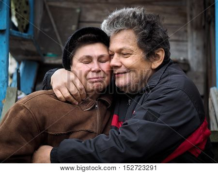 The man affectionately hugs a woman. People aged. Old wooden house