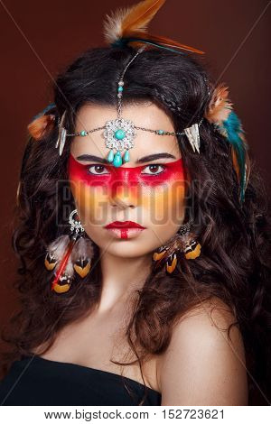 Beautiful squaw in ethnic jewelry . Close up portrait. Native american costume. Portrait of a woman with a painted face. Creative makeup and bright style.