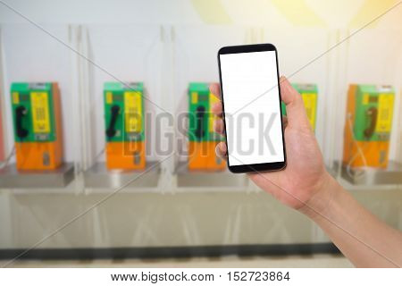 human hand hold smartphone tablet cell phone with blank screen on blurry obsolete phone booth concept of change in communication.