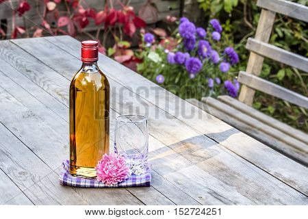 Bottle of whiskey and a glass with flower on the old table in autumn garden's