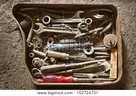 Old vintage rusty metal box with wrenches screwdrivers and other tools mechanics. Contrast light. View from above.