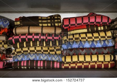 Row of colorful patterned woolen blankets stacked on a shelf.