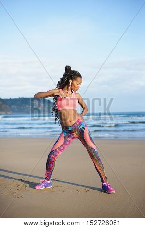Sporty brazilian woman dancing and having fun at the beach. Black happy dancer enjoying music rhythm.