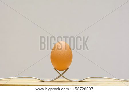 Egg on a fork on a wooden floor.