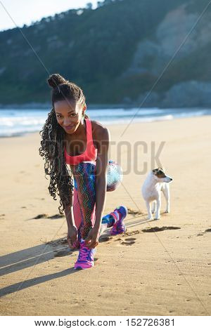 Sporty woman lacing sport footwear before running and exercising at the beach with her dog. Black beautiful runner training outdoor.