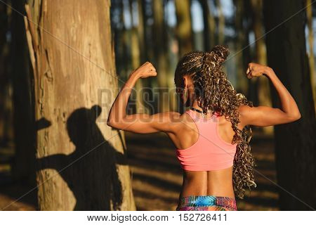 Workout and fitness lifestyle success. Black woman showing biceps for training motivation.