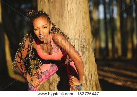 Tired cheerful sporty woman taking a workout rest for breathing and recovery. Black beautiful athlete training in nature under sunrise morning light.