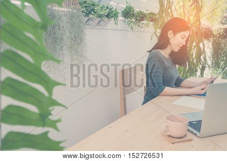 Office table with laptop and Asian woman watching on tablet Education online office place on tree garden. Selected focus on side laptop. Vintage effect style pictures.