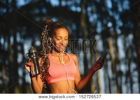 Cheerful sporty brazilian sportswoman taking a fitness workout rest for drinking water and listening music. Black female athlete wearing earphones.