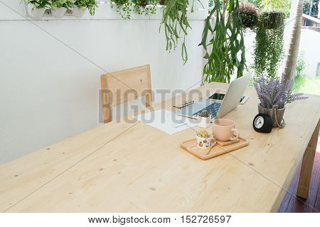 office table with laptop tablet and purple lavender flower on pot office work place at tree garden. Relax time and dessert cake at garden.