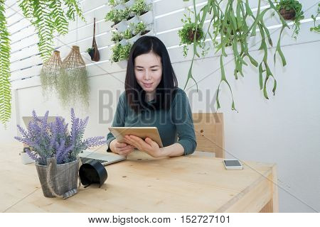Asian woman finding data on tablet at tree garden relax time on office corner shopping online concept at home. woman find job on tablet at home.
