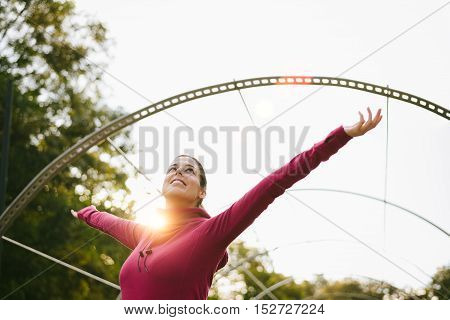 Sporty blissful woman raising arms against golden morning sun. Female athlete celebrating fitness workout goals and success at urban park.