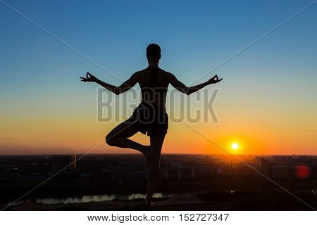 Silhouette of sporty woman practicing yoga in the park at sunset - half lotus tree pose. Sunset light, golden hour. Freedom, health and yoga concept