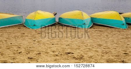boats lying upside down on the sandy beach