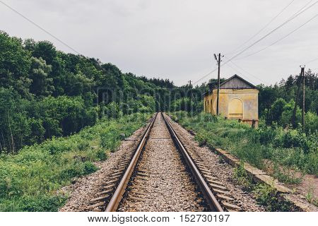 railway tracks in the woods and a house with an edge