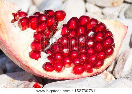 Slice of pomegranate fruit on light stone background. Organic fresh juicy product