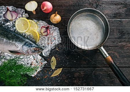 Fresh whole salmon fish on foil sheet with veggies and spices with frying pan ready for cooking. Flat lay