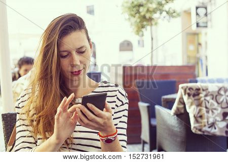 Young lady on bar table using a smart phone dialing or using some app or sending sms casual look stripes shirt and light make up hipster vintage color variation