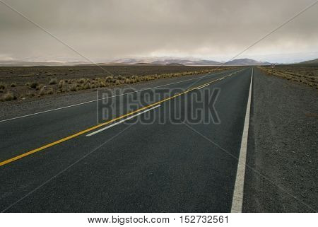 Spacious cloudy landscape crossed by empty road