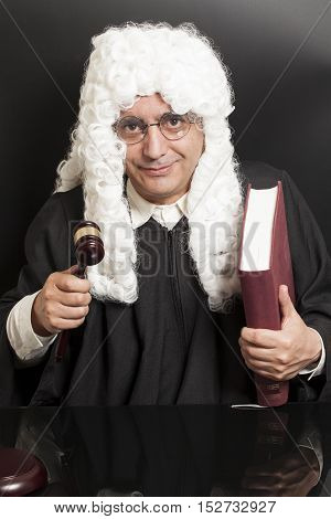 Portrait Of Male Lawyer Holding Judge Gavel And Book on black background