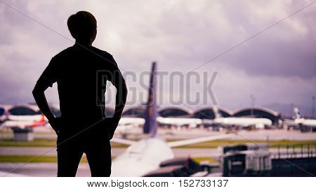 A man standing with silhouette foreground over the blurred airport background