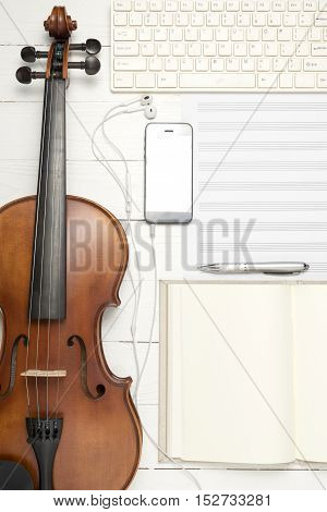 violin with music paper note notebook and smart phone on white wood background