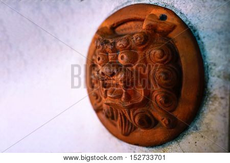 Shisa Lion charm plate on the white wall can found this at Okinawa Japan