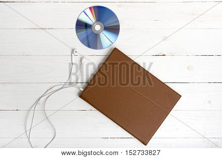 top view of book dcd disc and earphone on white wood background