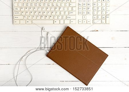 top view of keybard computer with notebook and earphone on white wood background