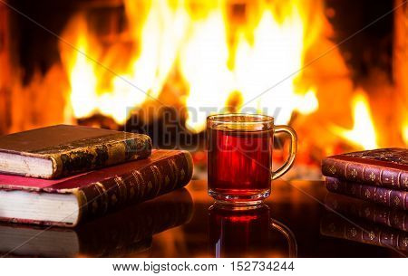 Glass mug of hot drink or alcoholic drink or mulled red wine and antique books in front of warm fireplace. Magical relaxed cozy atmosphere near fire. Autumn or winter concept