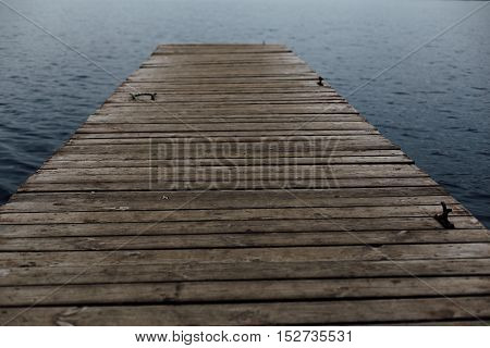 old wooden pier on the background of a dark lake water