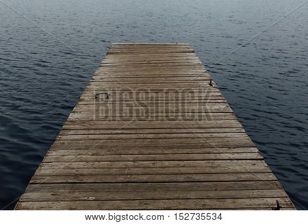 old wooden pier on the background of a dark lake water concept