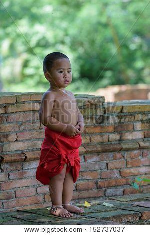 Asian Thai boy look and smile he dress thai local dress with saliva on his neck and breast.