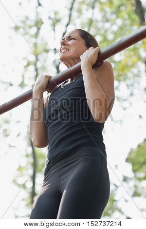 Female athlete doing chin-ups outdoors, color image