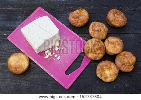 Fresh baked muffins with cheese on dark wooden background top view