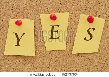 Yes answer Three yellow notes on a cork board with the word Yes