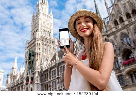 Young woman showing phone with white screen on the town hall building background in Munich