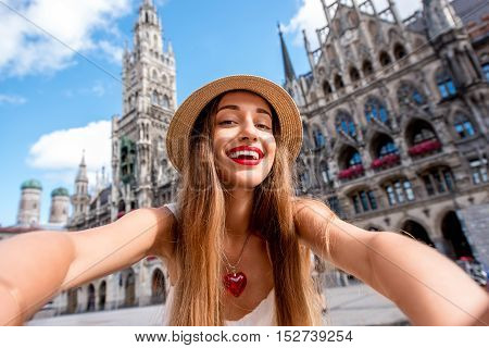Young female tourist making selfie photo on the central square in front of the town hall building in Munich. Having a great vacation in Germany