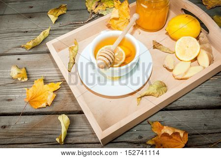 Autumn warming ginger tea with honey and lemon on a tray, a cozy breakfast or snack. At the rustic wooden table. With autumn yellow leaves around.