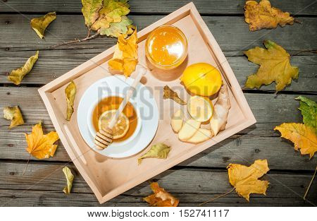 Autumn warming ginger tea with honey and lemon on a tray, a cozy breakfast or snack. At the rustic wooden table, top view. With autumn yellow leaves around.