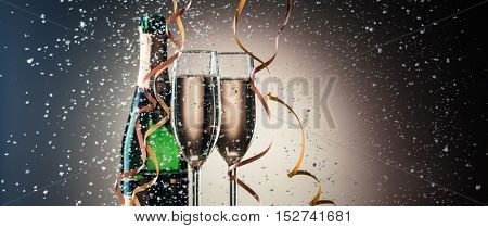 Two wineglasses with champagne closeup, bottle, ribbons and snowflakes