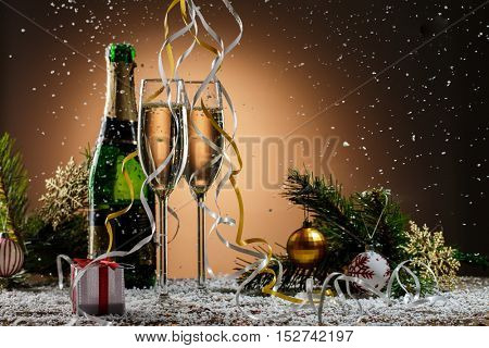 Champagne, fir-tree branches with toys and gift box