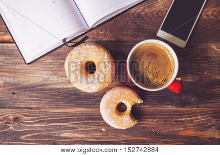 Donuts and coffee lying on rustic wooden background with open notepad and mobile phone. Top view. Retro toned picture.