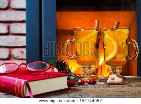 two glasses of tea and open book at romantic fireplace