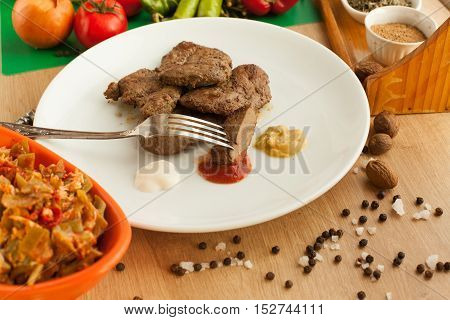 Roast meat served with ketchup, mayonnaise and mustard, sliced piece of meat hanging on a fork. Cooked liver with spices and salad on white plate standing on he table.