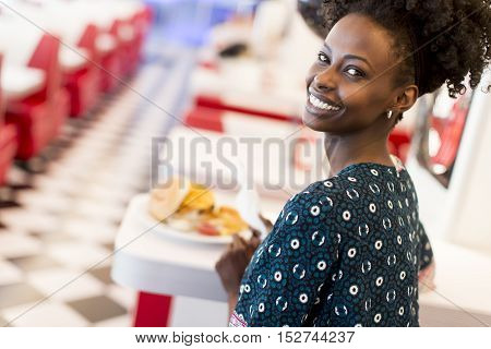 Young african american woman eating in the diner