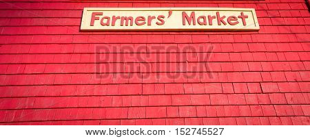 Farmer's market sign on a background on red shingles