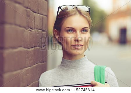 Close-up of girl with glasses to have brick wall on street