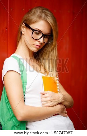 Girl in glasses close-up at Brown wooden walls